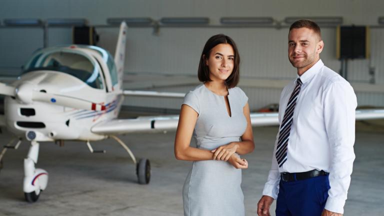 Frau und Mann vor einem Flugzeug im Hangar