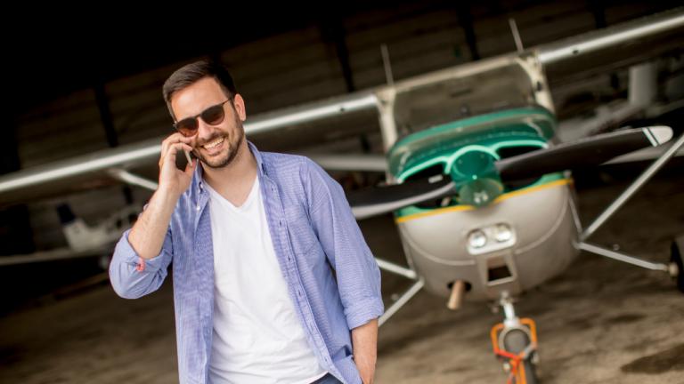 Pilot telefoniert vor Flugzeug