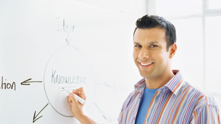 Lehrer an Whiteboard lachend